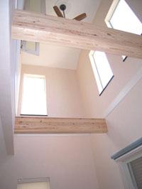 2階のホールと寝室に繋がった吹抜け は外からの光を明るく取り入れる(1階リビング)