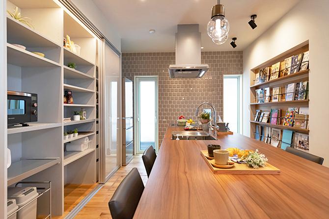 タイル壁や造り付けの本棚を取り入れたアイランドキッチン