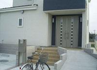 ▲広い土地は前庭を大きくとってアプローチと駐車場に。ゆるやかな玄関アプローチからはバイクが収納できる。