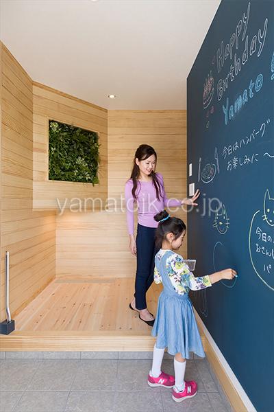 [神戸市北区]ダブル断熱仕様でエアコン1台で全館空調するZEH(ゼロエネルギーハウス)ヤマト住建モデルハウスの黒板壁紙の玄関