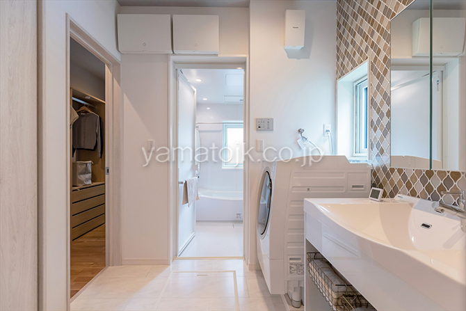 [群馬県太田市]ダブル断熱仕様でエアコン1台で全館空調するZEH(ゼロエネルギーハウス)ヤマト住建モデルハウスのリビングと主寝室の2方向から出入りできる洗面室