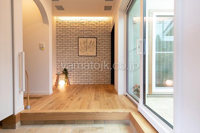 [群馬県太田市]ダブル断熱仕様でエアコン1台で全館空調するZEH(ゼロエネルギーハウス)ヤマト住建モデルハウスの中庭を望む玄関ホール