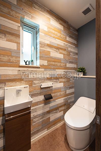 [神戸市西区]ダブル断熱仕様のZEH(ゼロエネルギーハウス)ヤマト住建モデルハウスのレンガ調アクセントクロスのおしゃれなトイレ