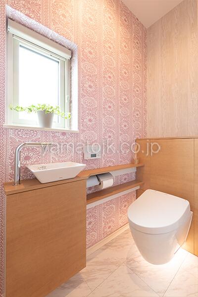 [滋賀県彦根市]ダブル断熱仕様で電気を自給自足するZEH(ゼロエネルギーハウス)ヤマト住建モデルハウスの上品なアクセントクロスのトイレ