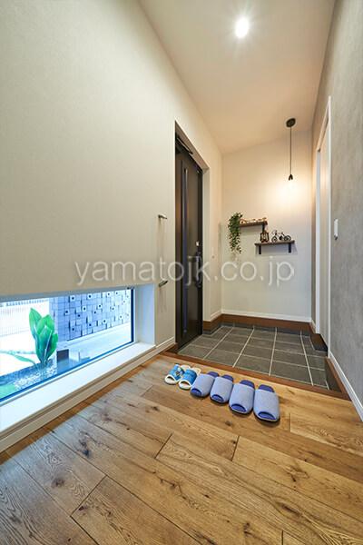 [埼玉県所沢市]ダブル断熱仕様のZEH(ゼロエネルギーハウス)ヤマト住建モデルハウスの地窓から坪庭が見える玄関