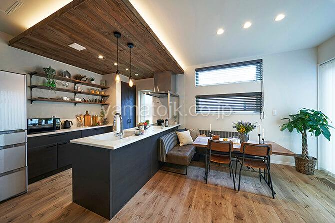 [埼玉県所沢市]ダブル断熱仕様のZEH(ゼロエネルギーハウス)ヤマト住建モデルハウスの下がり天井のキッチンとソファダイニング