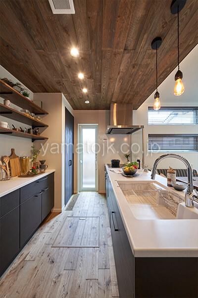 [埼玉県所沢市]ダブル断熱仕様のZEH(ゼロエネルギーハウス)ヤマト住建モデルハウスの木目調の天井の落ち着いた色合いのキッチン